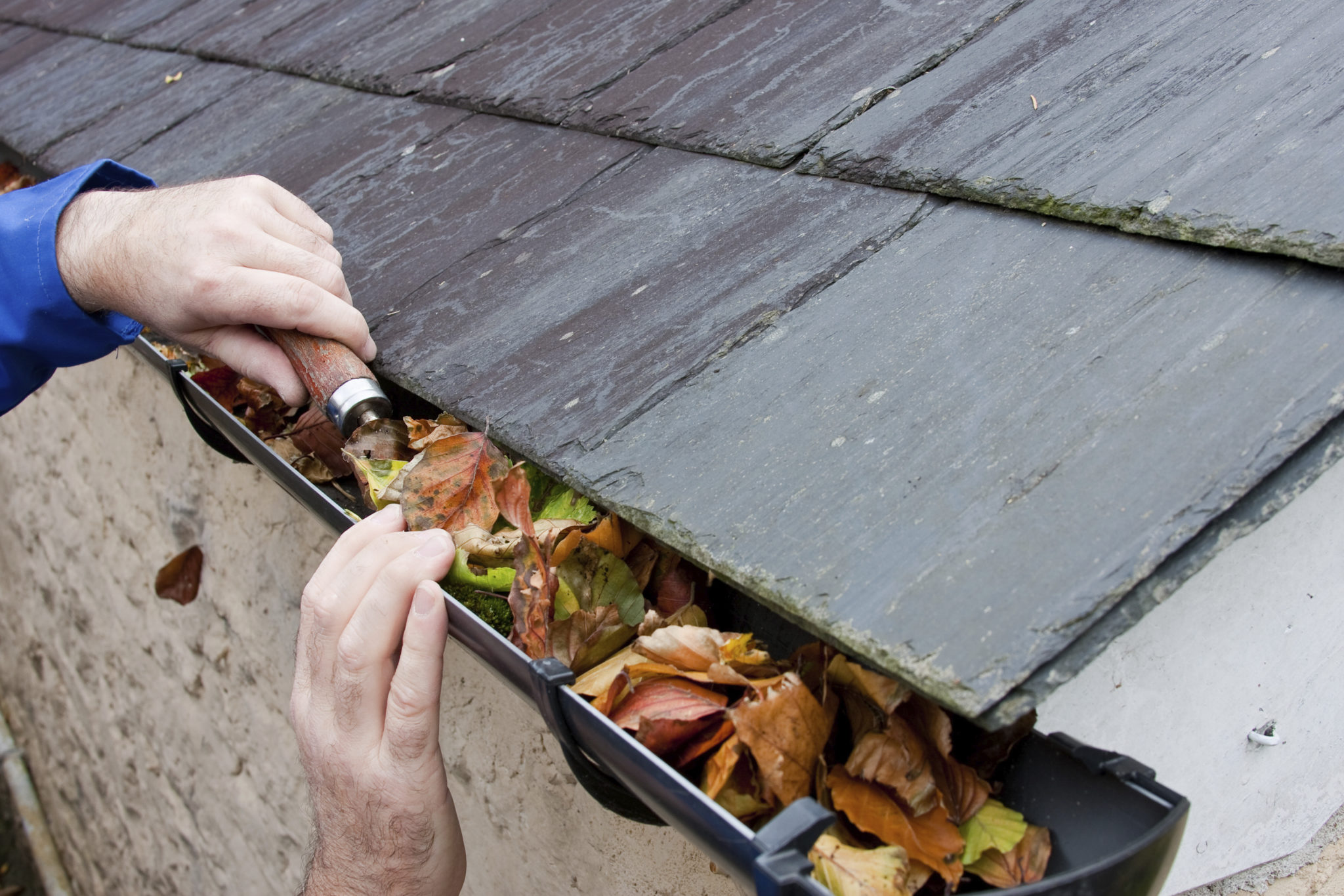gutters clogged, hand cleans with tool